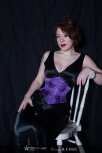 Model in a black satin dress and violet corset